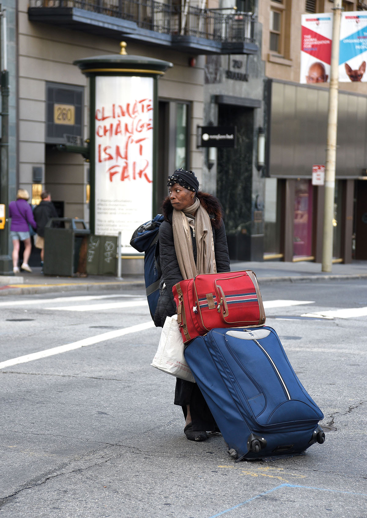 SAN FRANCISCO, CALIFORNIA - SEPTEMBER 12, 2018: A woman drags her possessions packed into suitcases and a backpack across a busy intersection in San Francisco, California. (Photo by Robert Alexander/Getty Images)